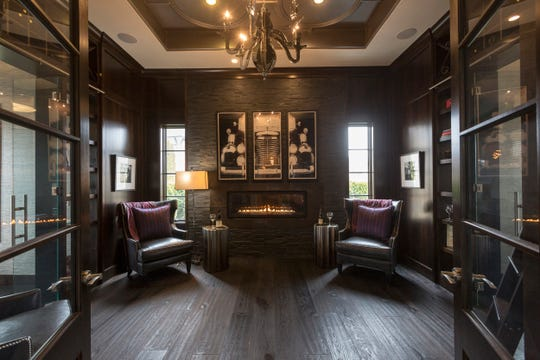 The wine lounge is a meeting place between his-and-her offices. One bookshelf is a secret door to the owner's wine collection. Visible through the French doors is some of the formal, entertaining part of the  Oakland Township home.