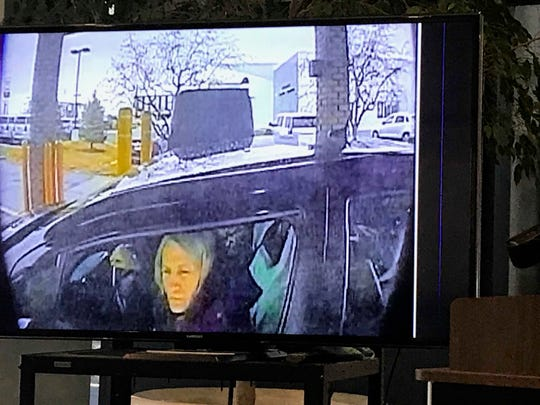 Macomb County Prosecutor Eric Smith displays a photo from a surveillance video that he said shows former county clerk Karen Spranger stealing money from an elderly woman's bank account.