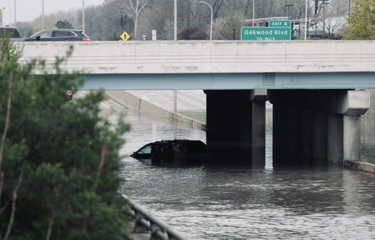 A car is seen stranded in flood water underneath the Outer Drive overpass on Southfield Freeway in Dearborn on Wednesday, May 1, 2019.