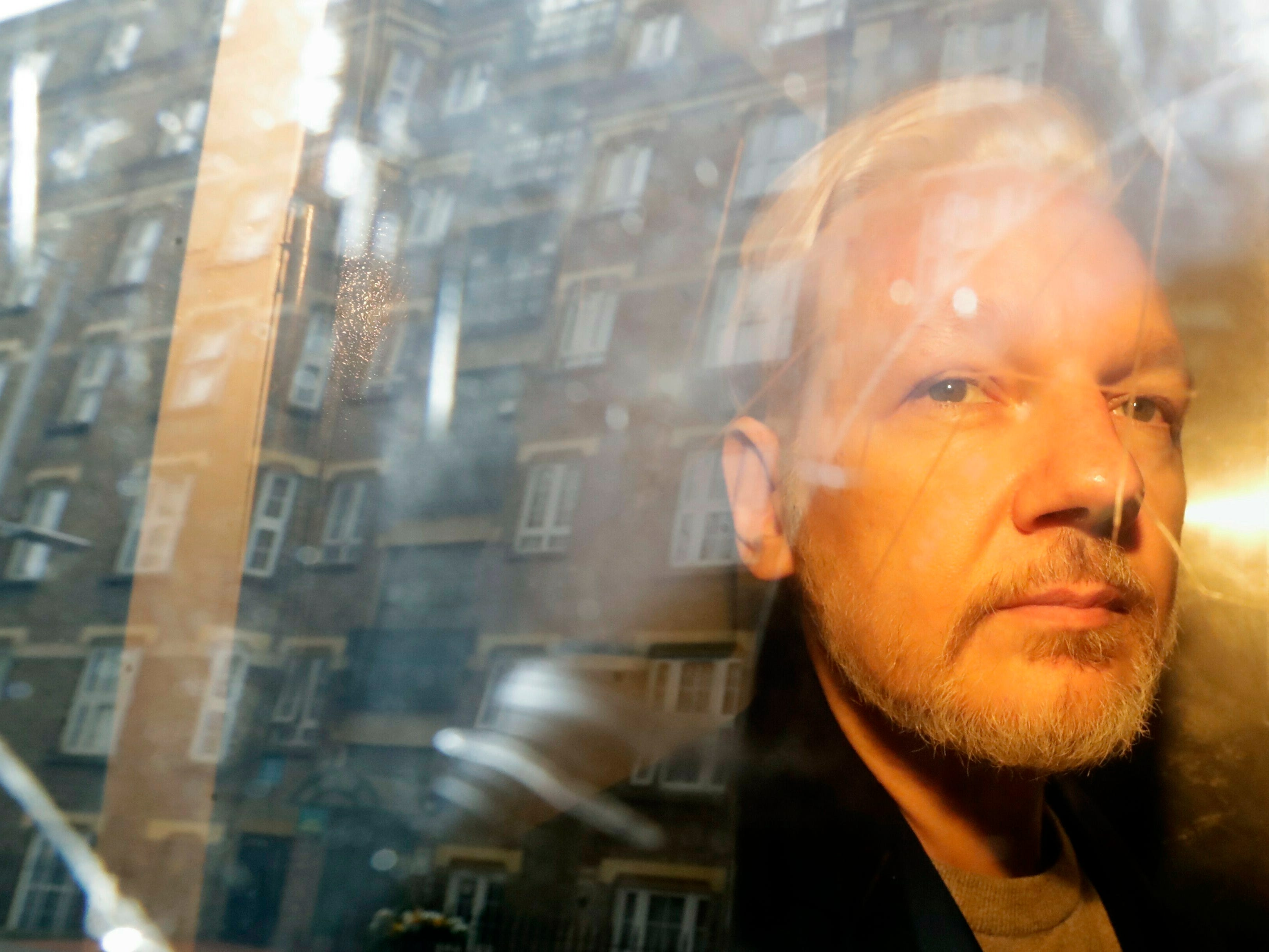 Buildings are reflected in the window as WikiLeaks founder Julian Assange is taken from court, where he appeared on charges of jumping British bail seven years ago, in London, Wednesday May 1, 2019. Assange has been jailed for 50 weeks for breaching his bail after going into hiding in the Ecuadorian embassy in London.
