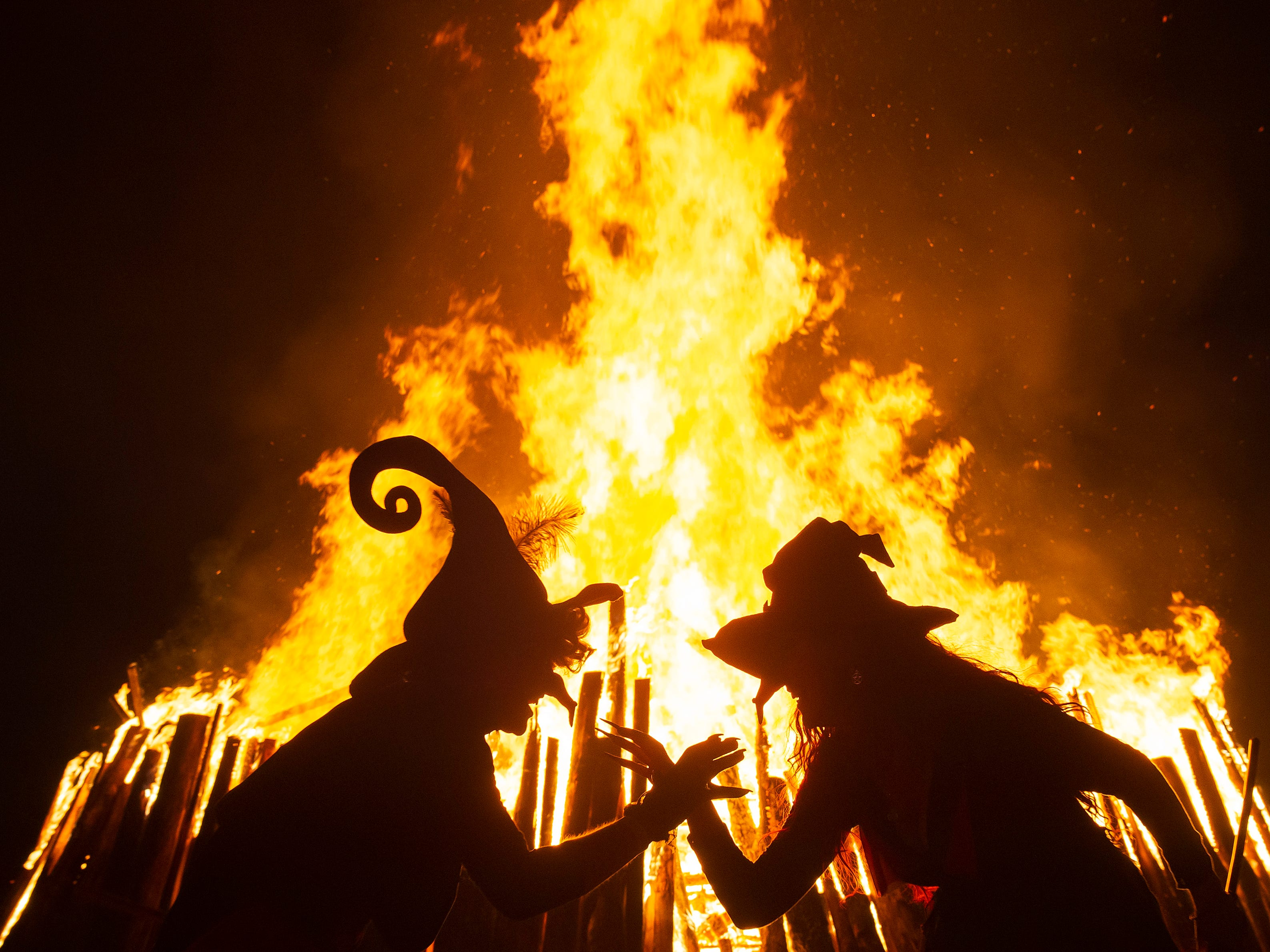Women dressed as witches dance in front of the fire during the Walpurgis night in Erfurt, Germany, Tuesday, April 30, 2019. Costumed devils and witches meet to celebrate Walpurgis Night, a traditional religious holiday of pre-Christian origins. The event is named after St. Walburga, an English nun who helped convert the Germans to Christianity in the 8th century.