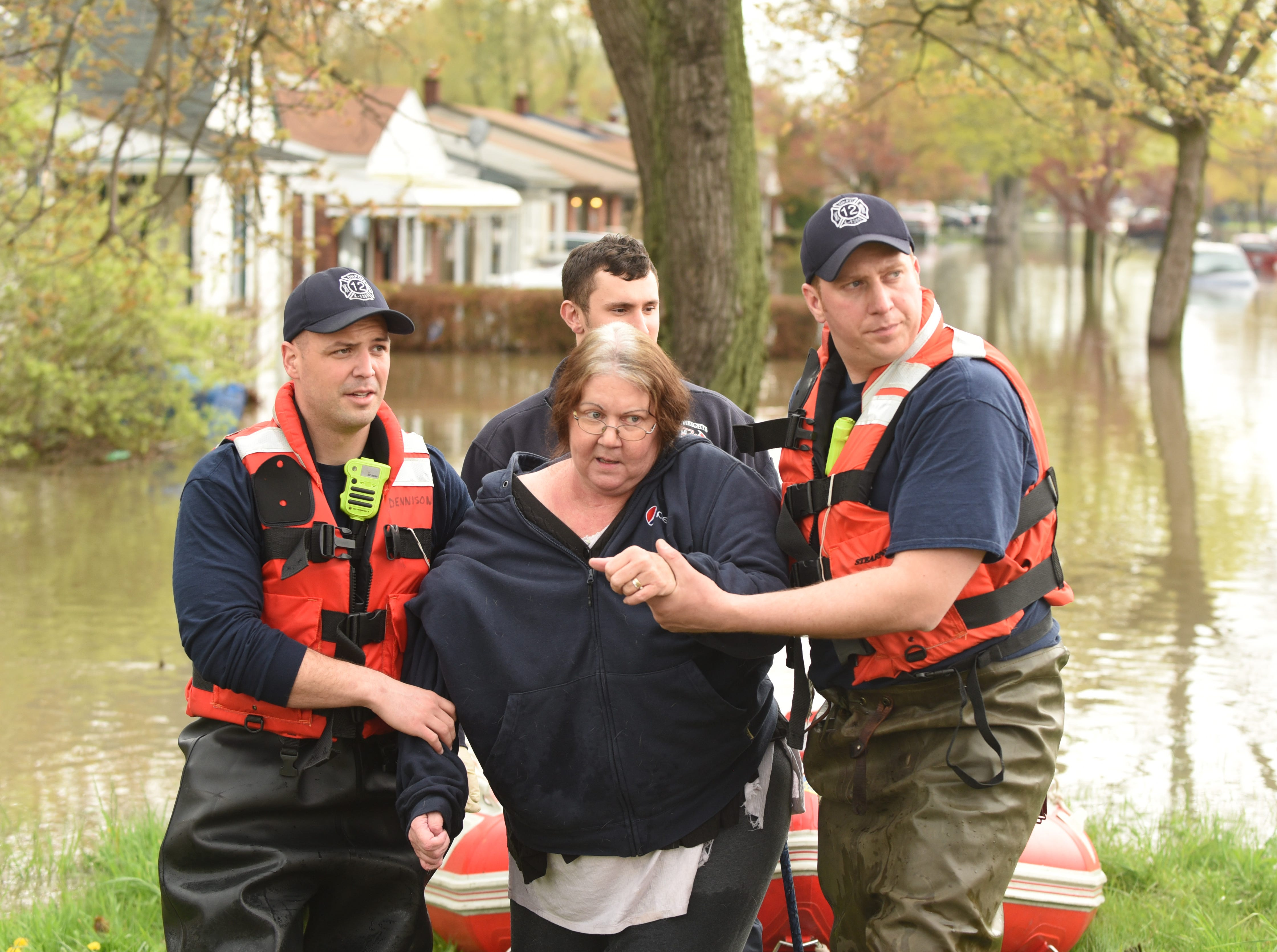 Dearborn Heights firefighters rescue Christine Wetzel from her flooded home along Currier Street.