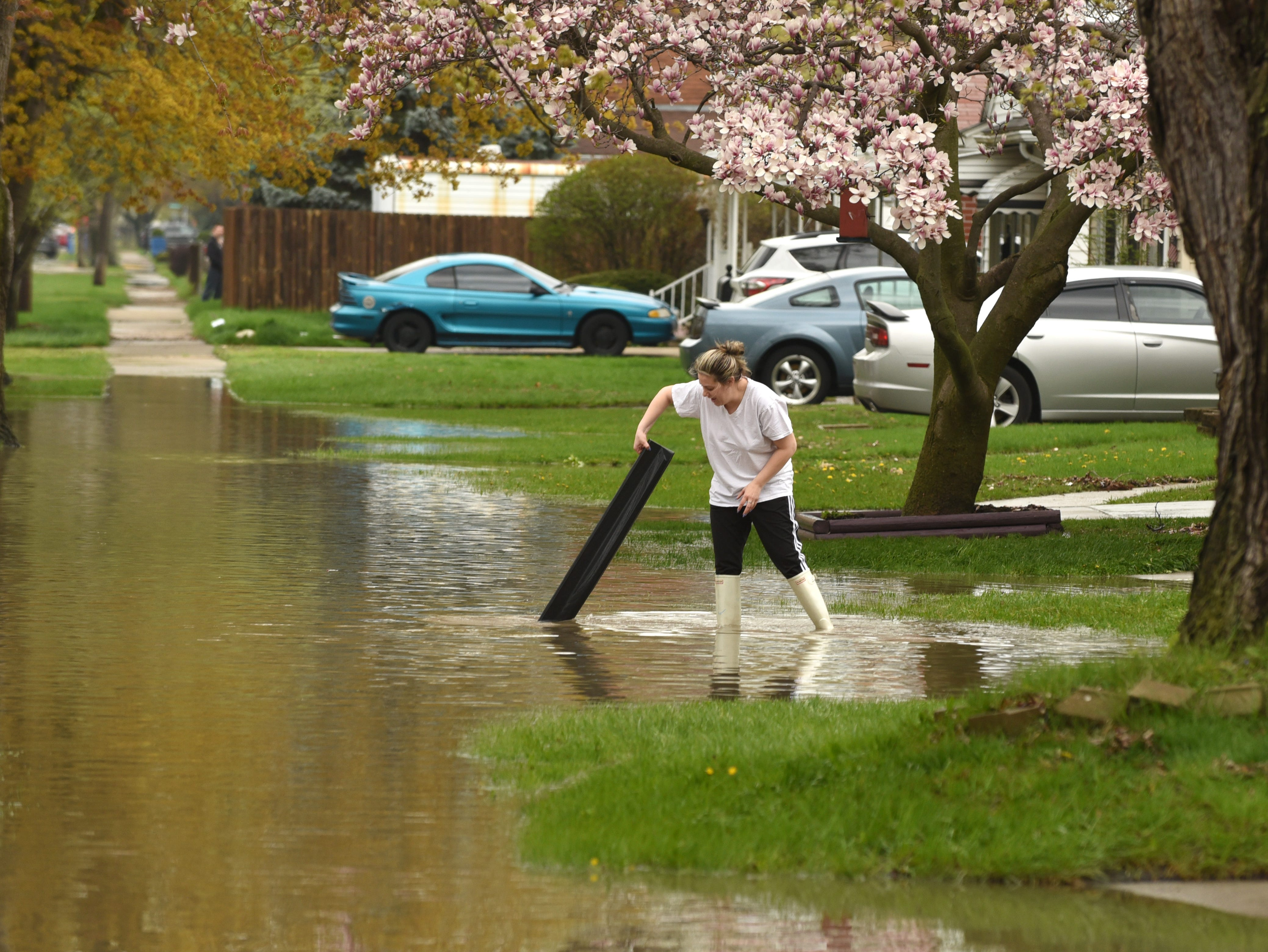 A woman clears debris from a storm drain along Monroe Street in Dearborn Heights.