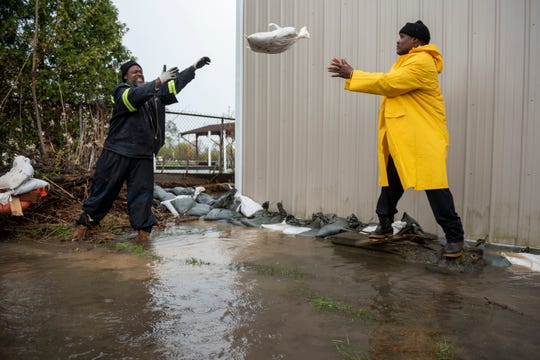 Detroit city employees Myron Quarles, left, and Lorenzo Colbert place sandbags around a residence on Klenk St. to stop canal flooding on Klenk Island in Detroit.