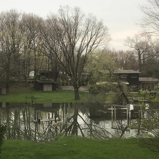 Water floods a yard and dock on Thorofare Canal in Grosse Ile.