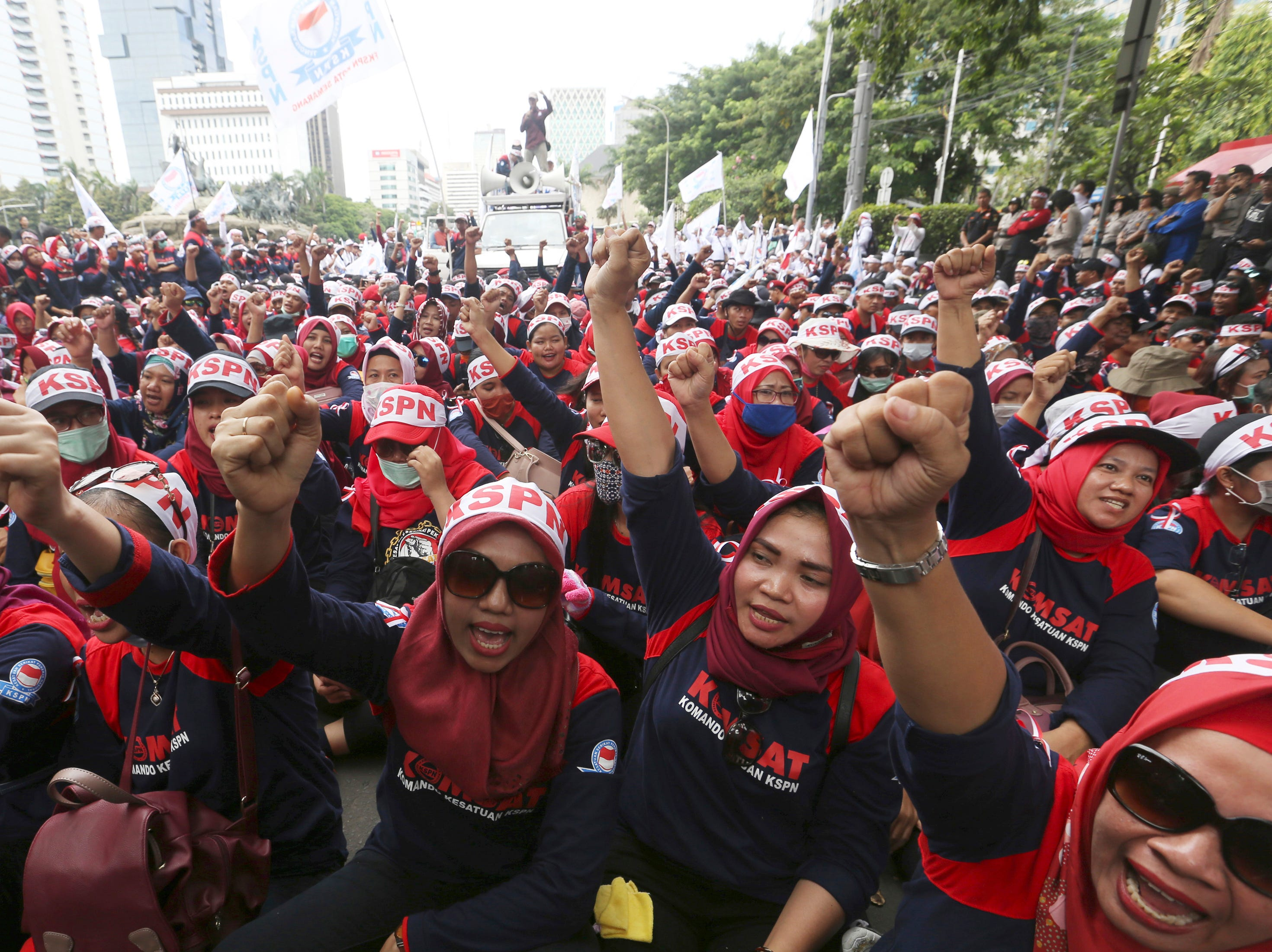 Workers shout slogans during a May Day rally in Jakarta, Indonesia, Wednesday, May 1, 2019. Thousands of workers attended the rally urging the government to raise minimum wages, ban outsourcing practices, provide free health care and improve working conditions.