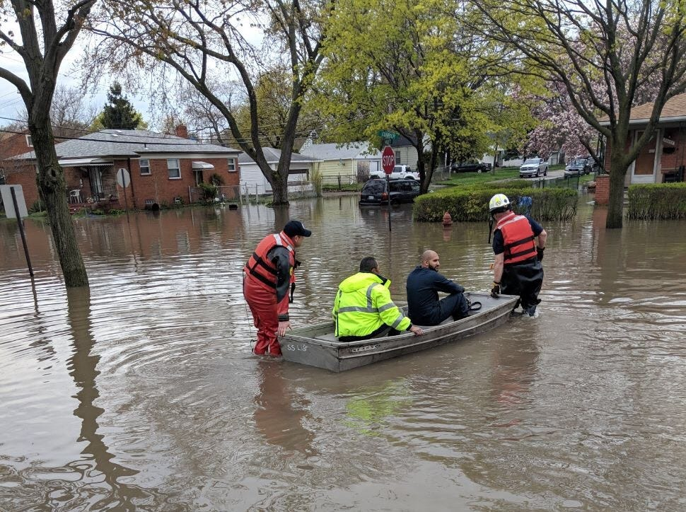 """Dearnborn Heights resident Maria Rodriguez-Torres took this photo of her neighbors rowing through the flooded streets of her neighborhood at Telegraph and Van Born. She has 3-4 feet of water in her basement with a pump leading out to the backyard. """"I learned from the flooding in 2014 not to put anything of importance down in the basement, but the washer and dryer and heater… those are important,"""" she said. """"It's terrible. The water came from the main downstairs, but our backyard and cars are fine thank God."""""""