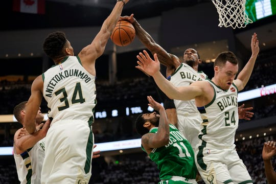 Boston's Kyrie Irving tries to shoot through a swarm of Milwaukee defenders during the second half of Game 2 on Tuesday.