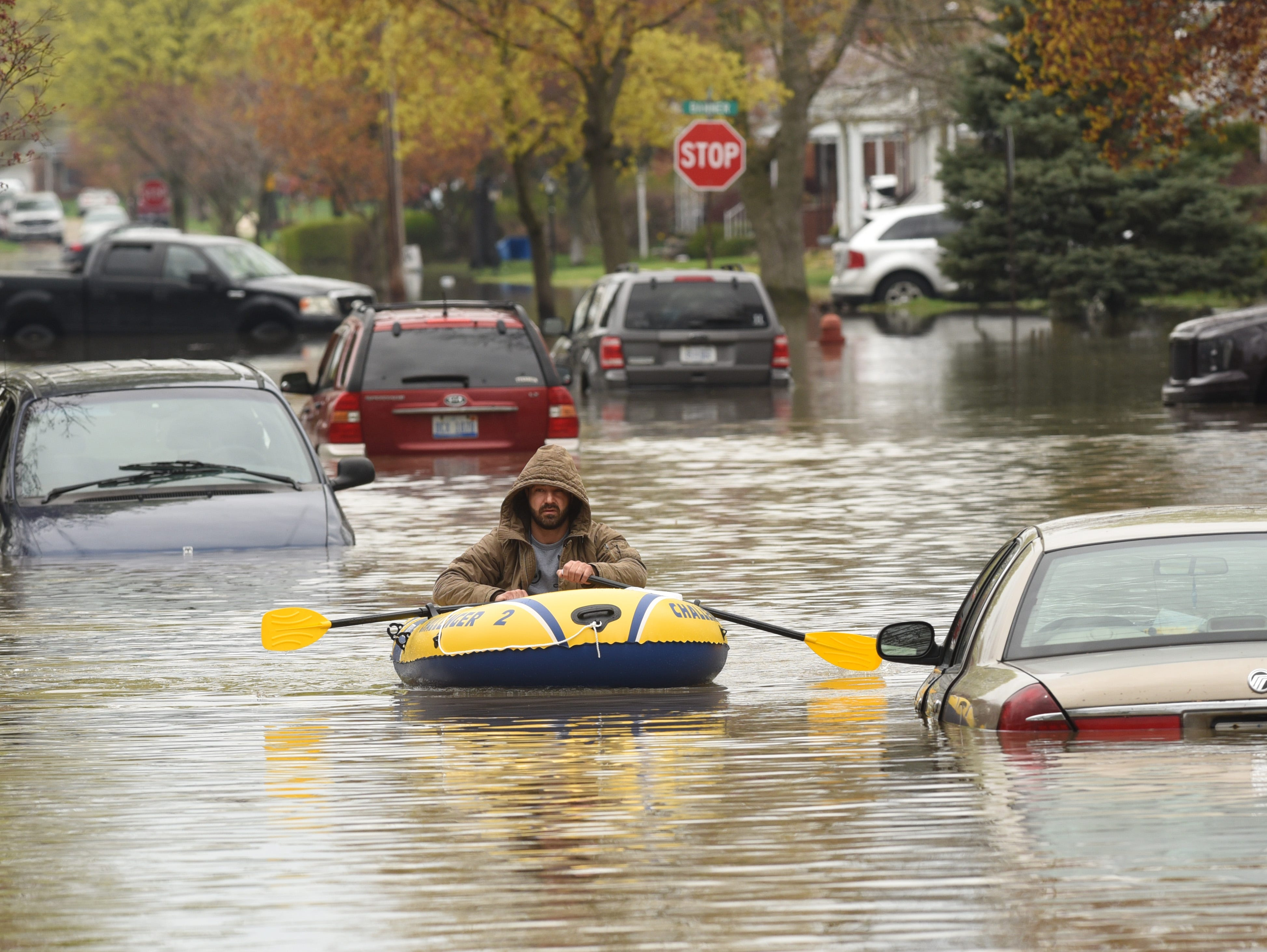 A Hanover Street resident paddles an inflatable boat around submerged vehicles on Currier Street in Dearborn Heights.