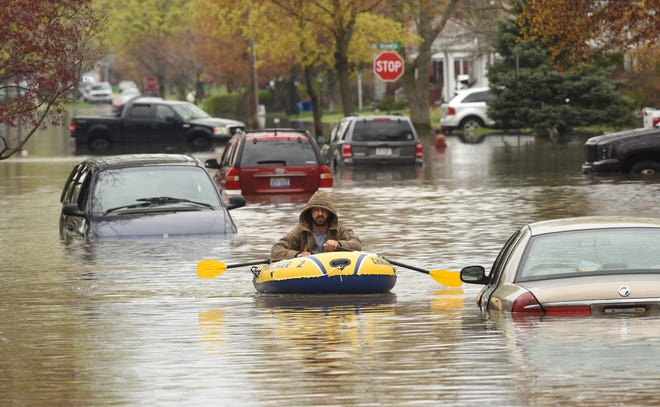 A Hanover Street resident paddles a raft along Currier Street in Dearborn Heights on Wednesday, May 1, 2019.  Several inches of record rainfall caused an already swollen Detroit River and Lake St. Clair, whose levels were at 30-year highs, to breach seawalls and flood neighborhoods.