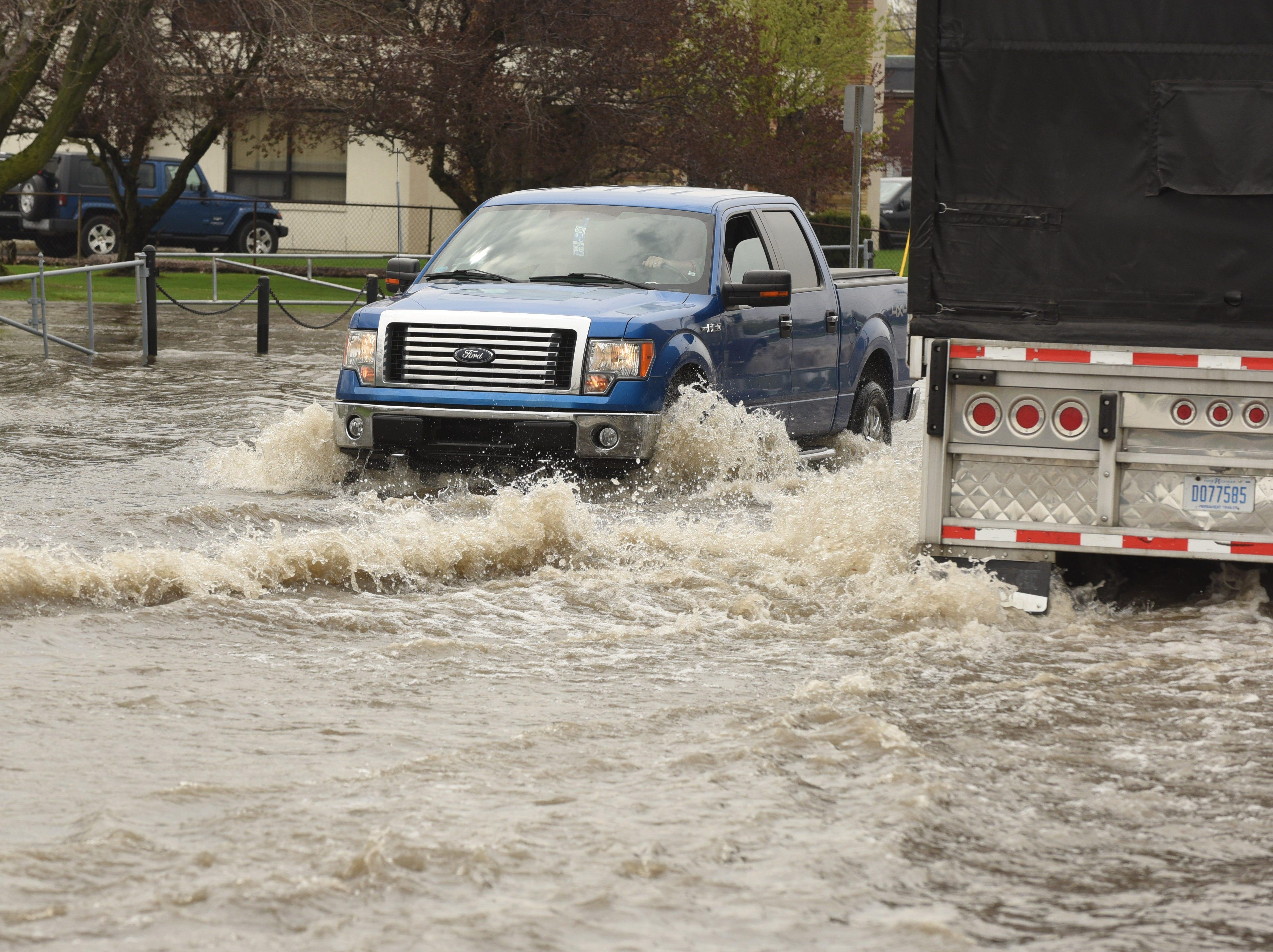 A motorist plows through flood waters along Monroe Blvd near Ecorse Road in Taylor.