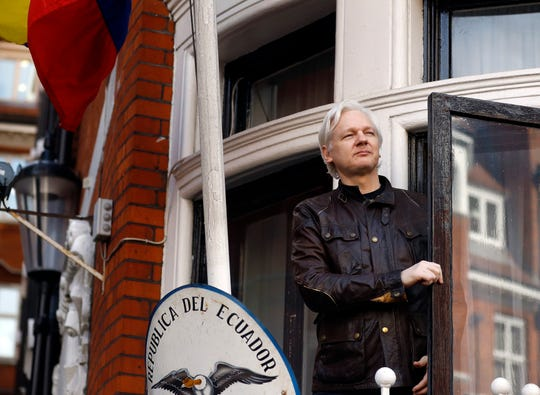 WikiLeaks founder Julian Assange looks out from the balcony in 2017 while claiming political asylum at the Ecuadorian embassy in London.