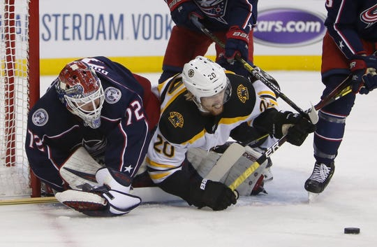 Blue Jackets goalie Sergei Bobrovsky, left, makes a save as Boston's Joakim Nordstrom collides with him during the first period of Game 3 on Tuesday.