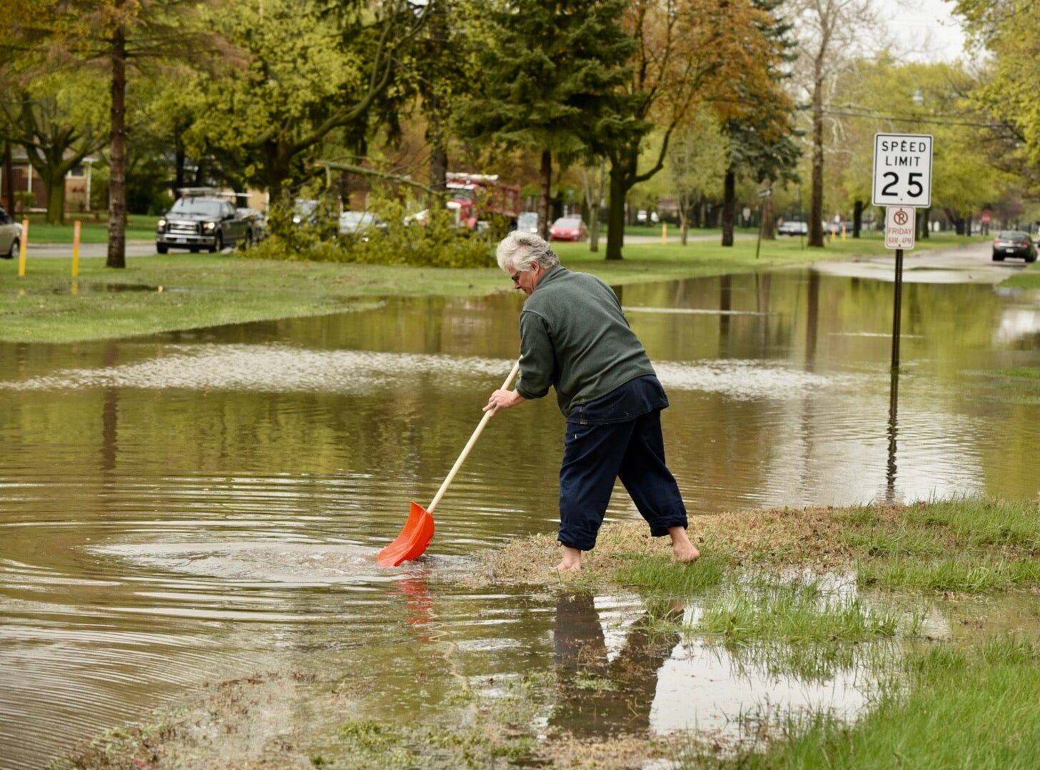 A Dearborn Heights resident tries to clear debris from a storm drain along Pinecrest Drive.