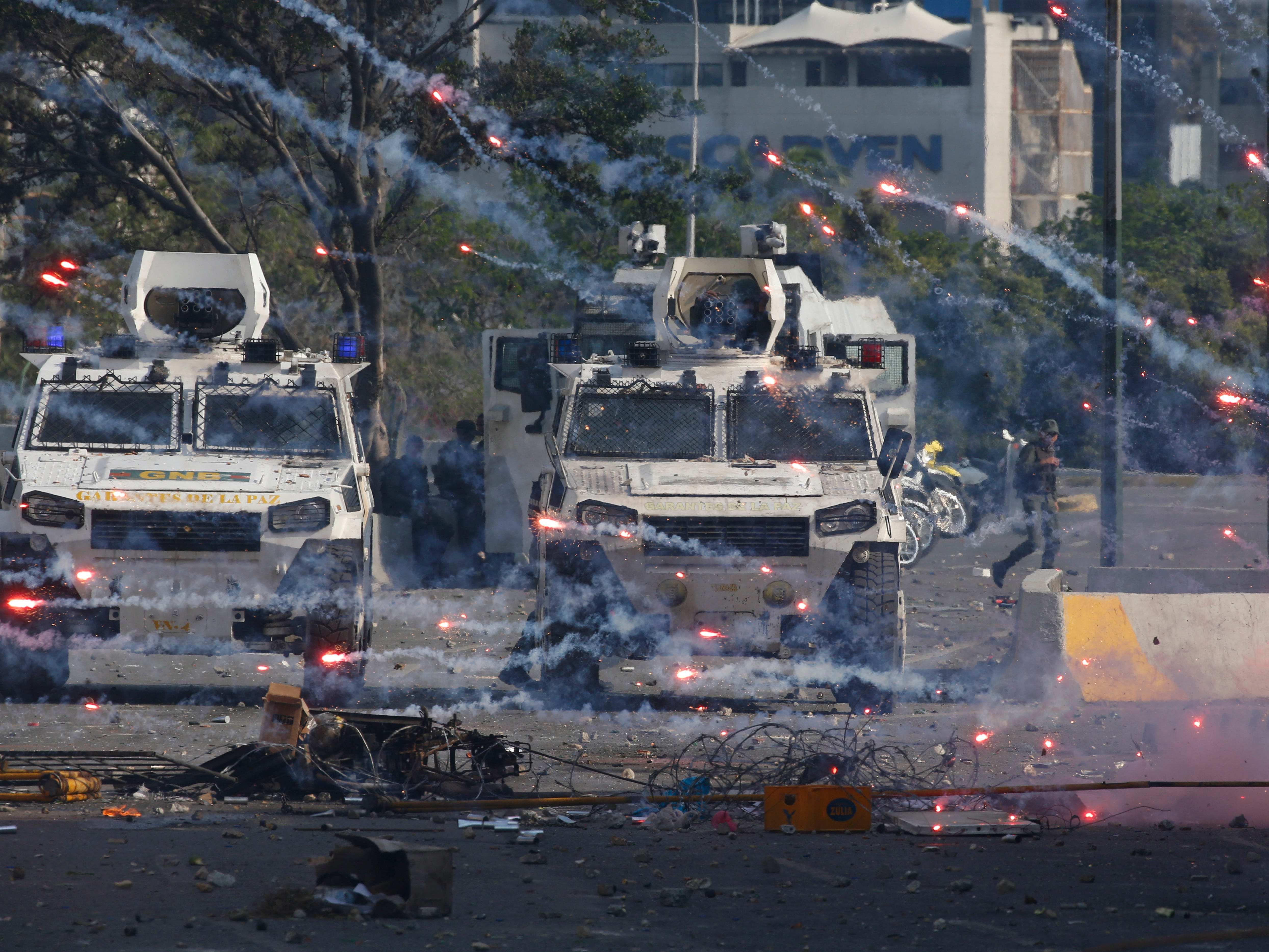 Fireworks launched by opponents of Venezuela's President Nicolas Maduro land near Bolivarian National Guard armored vehicles loyal to Maduro, during an attempted military uprising in Caracas, Venezuela, Tuesday, April 30, 2019. Opposition leader Juan Guaido took to the streets with a small contingent of heavily armed troops in a call for the military to rise up.