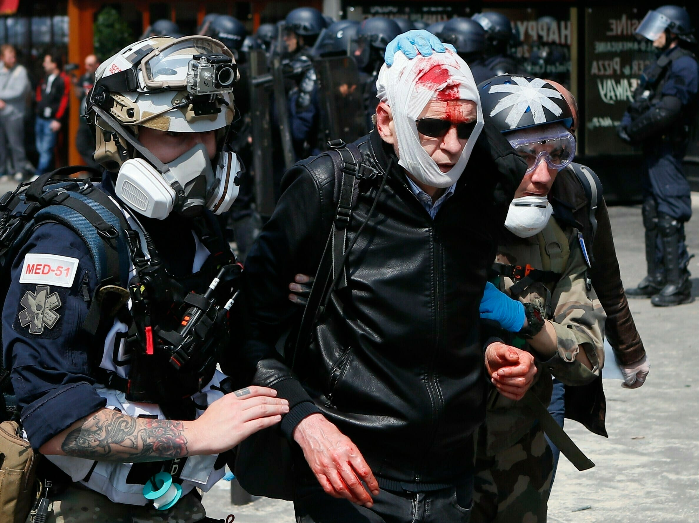 """A man, his face covered in blood, is helped to leave during a May Day demonstration in Paris, Wednesday, May 1, 2019. French authorities announced tight security measures for May Day demonstrations, with the interior minister saying there was a risk that """"radical activists"""" could join anti-government yellow vest protesters and union workers in the streets of Paris and across the country."""