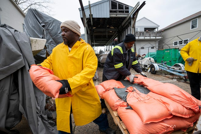 Detroit city employees Dwight Miles, left, and Myron Quarles remove sandbags off and place them around a residence on Klenk St. to stop canal flooding on Klenk Island, in Detroit.