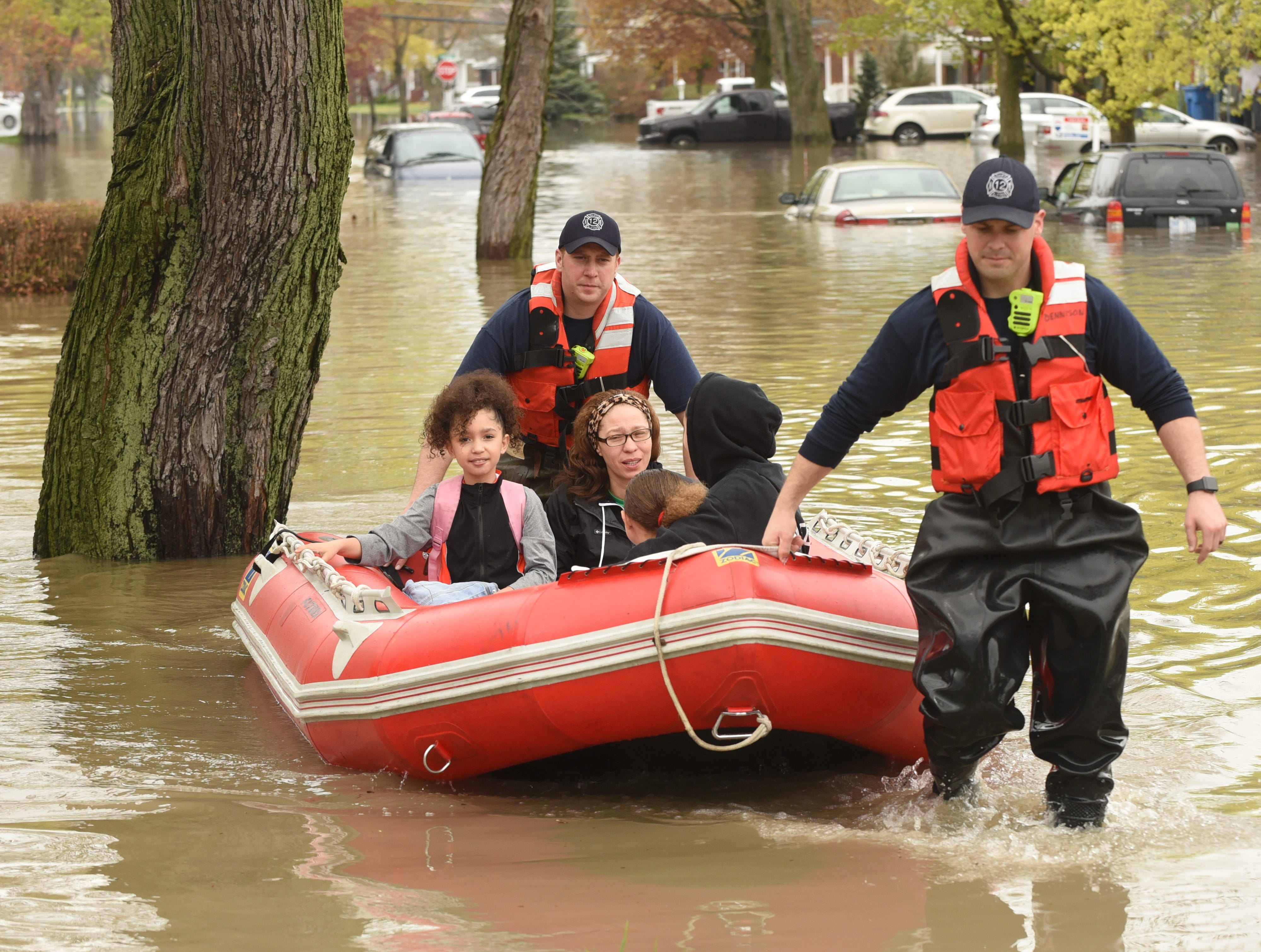 Dearborn Heights firefighters rescue members of the Clifton family from their flooded home along Currier Street in Dearborn Heights Wednesday.