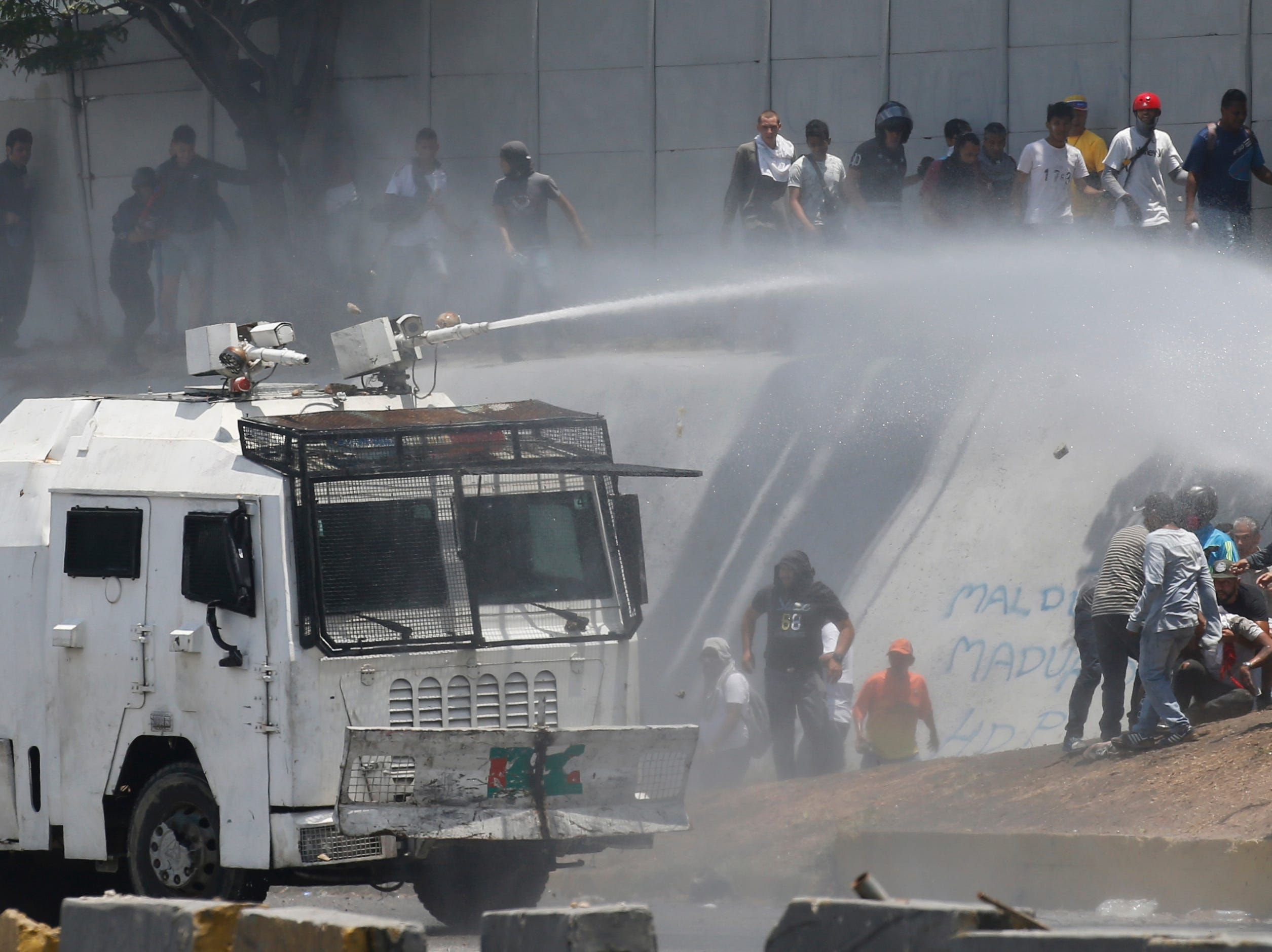A Bolivarian National Guard water canon sprays opponents of Venezuela's President Nicolas Maduro during an attempted military uprising and anti-government protests in Caracas, Venezuela, Tuesday, April 30, 2019. Venezuelan opposition leader Juan Guaido and opposition leader Leopoldo Lopez, recently released from prison, took to the streets with a small contingent of heavily armed troops early Tuesday in a bold and risky call for the military to rise up and oust Maduro.