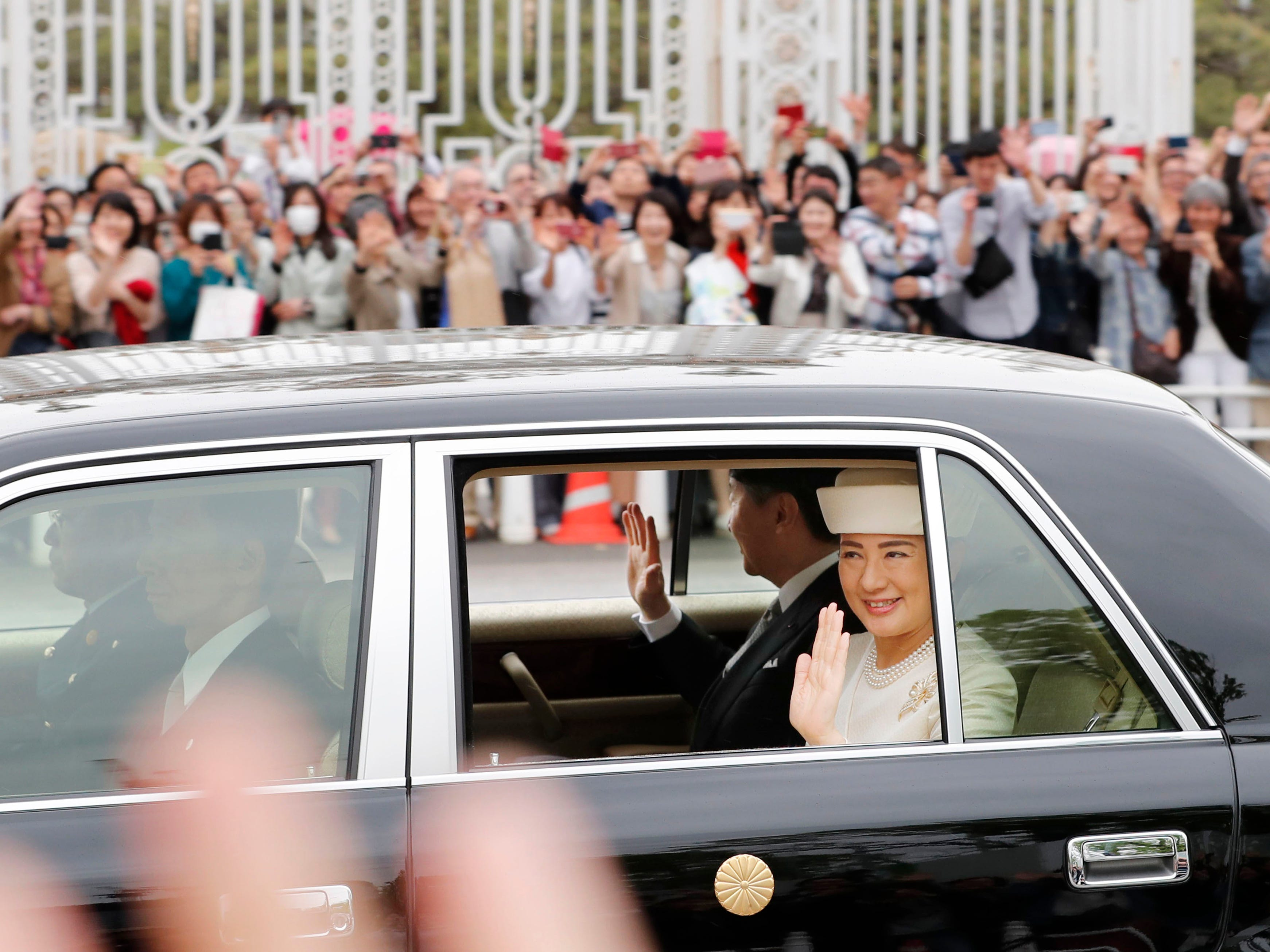 People gather as the car carrying new Emperor Naruhito and Empress Masako passes near state guest house in Tokyo Wednesday, May 1, 2019. Naruhito inherited the sacred sword and jewel that signaled his succession and pledged in his first public address Wednesday to follow his father's example by devoting himself to peace and sharing the people's joys and sorrows.