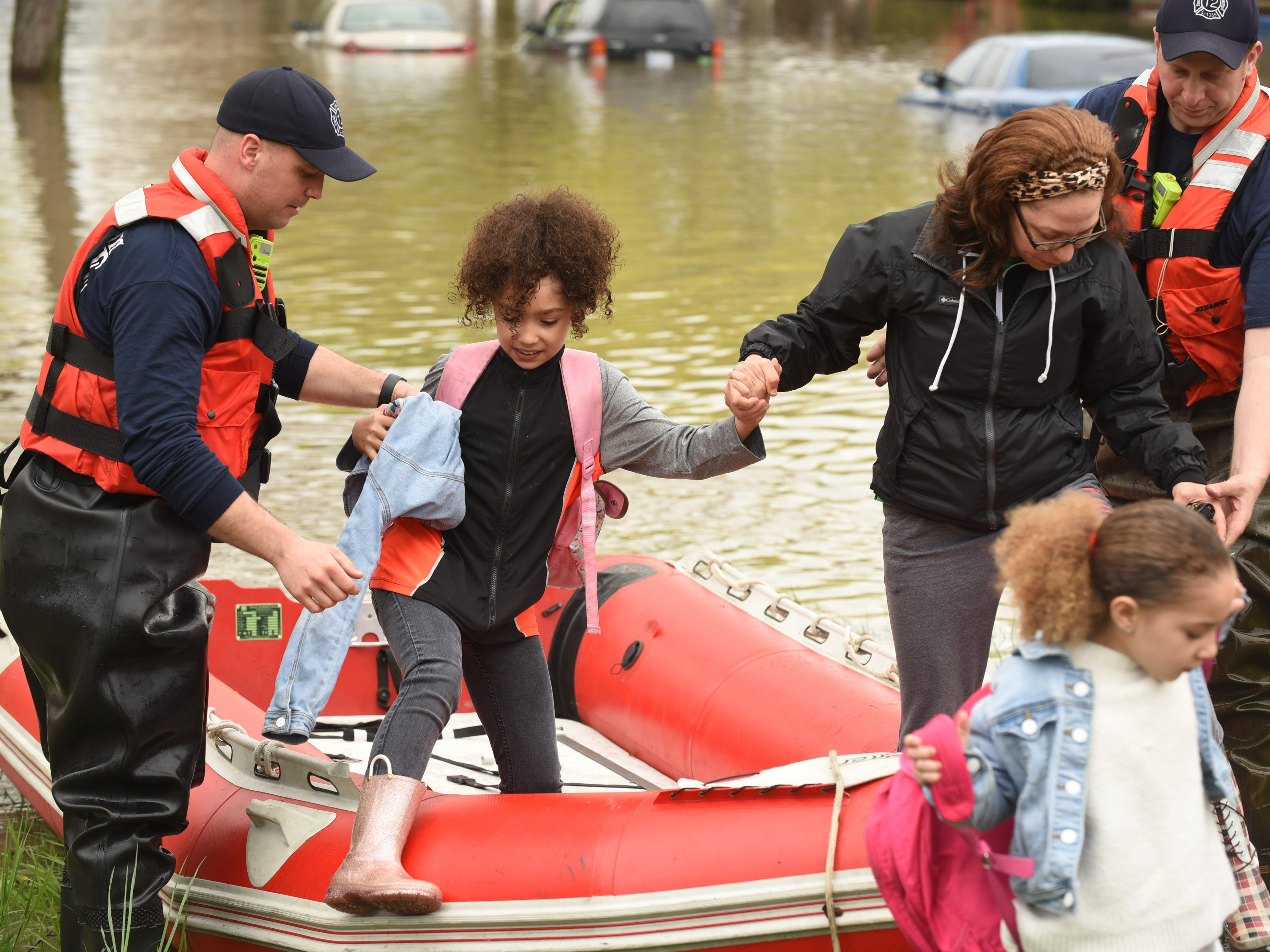 Dearborn Heights firefighters rescue members of the Clifton family from their flooded home along Currier Street in Dearborn Heights.