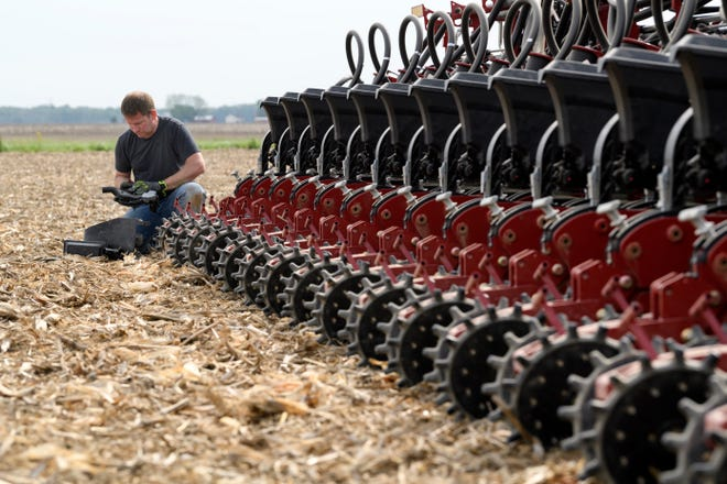 Eric Crews of Stahl Farms checks to make sure the farm's new Case IH Early Riser planting machine is working before continuing to plant soybeans on a field along Old Boonville Highway in Evansville, Ind., on May 1, 2019.