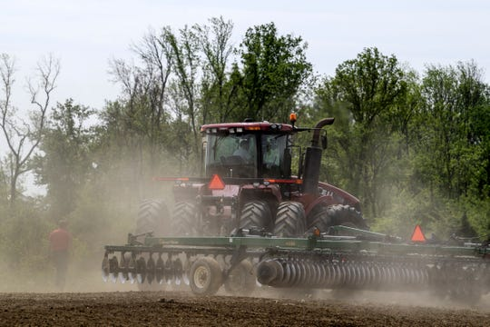 Patrick Howard uses a disc harrow to till soil to prepare the field for corn planting in Boonville, Ind., Wednesday, May 1, 2019.