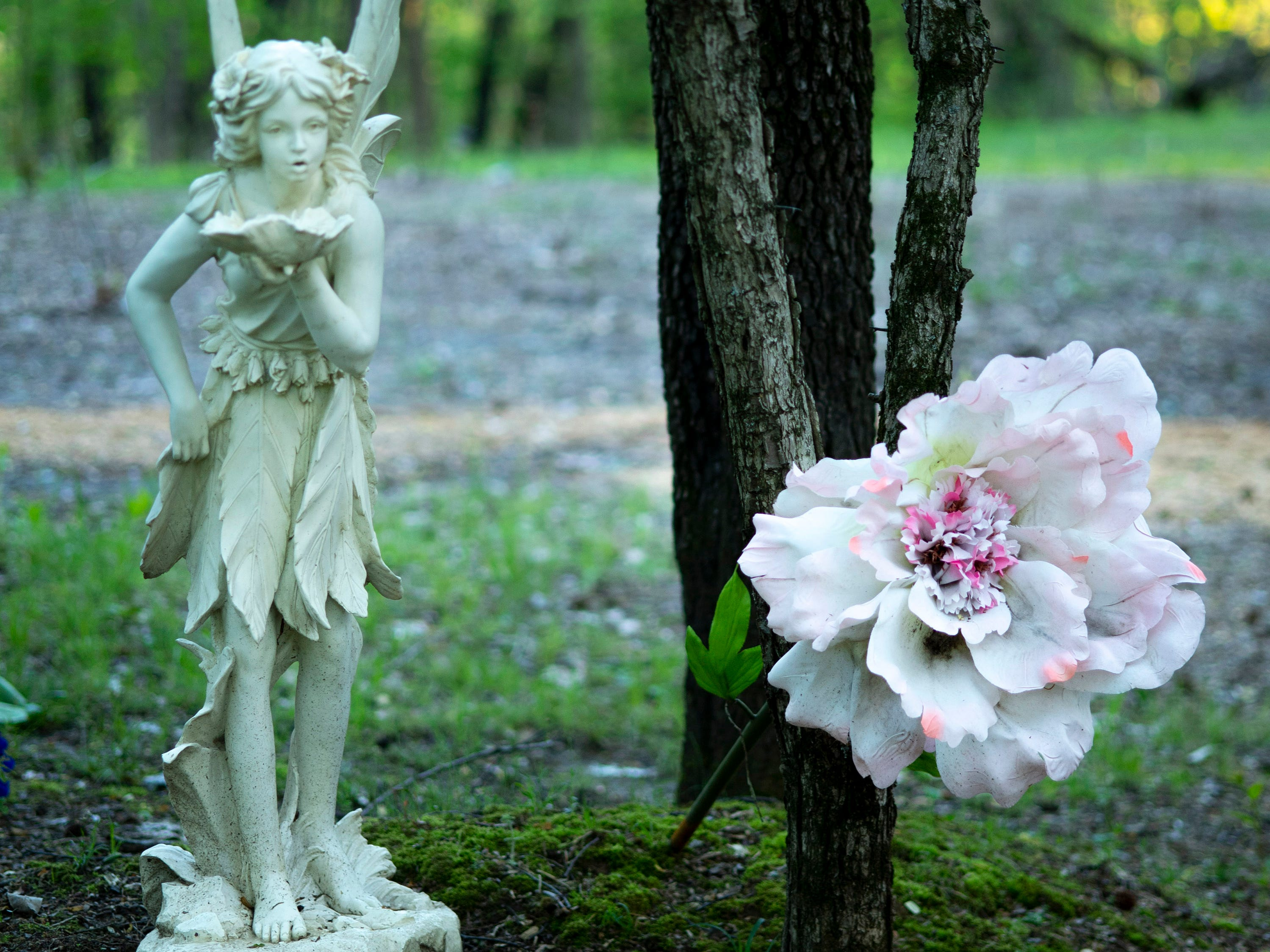 A fairy and an over-sized azalea decoration at the Azalea Path Arboretum and Botanical Gardens in Pike County, Ind., Friday, April 26, 2019. The facility was started by Beverly Knight in 1979 on 15 acres and has grown to more than 60 acres and has about 500 varieties of the flower.
