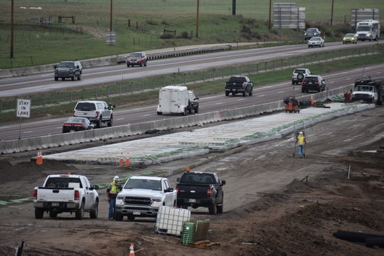 Vehicles on Interstate 25 just north of Colorado Highway 392 whiz past road crews adding a lane as part of the North I-25 Express Lane project.