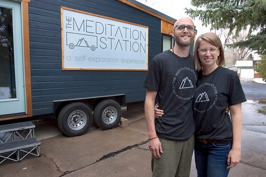 """Co-founders of The Meditation Station, Tate McTate, left, and his wife, Sarah, are pictured outside of their 200-square-foot mobile, custom-built """"tiny"""" meditation studio outside their home in Laporte, Colorado on April 30, 2019."""