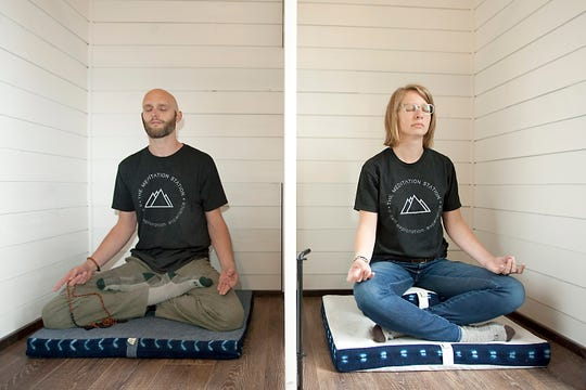 """Co-founders of The Meditation Station, Tate McTate, left, and his wife, Sarah, meditate in individual cubicles inside their mobile, custom-built """"tiny"""" studio outside their home in Laporte, Colorado on April 30, 2019."""