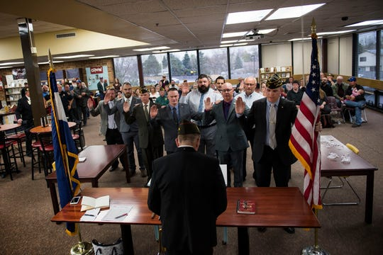 Members of the new Berthoud VFW Post 12189 - SPC Gabriel Conde Memorial take an oath of installation from Colorado Veterans of Foreign Wars state commander Steve Kjonaas, center, at the chartering ceremony for the post on Tuesday, April 30, 2019, at Berthoud High School in Berthoud, Colo.