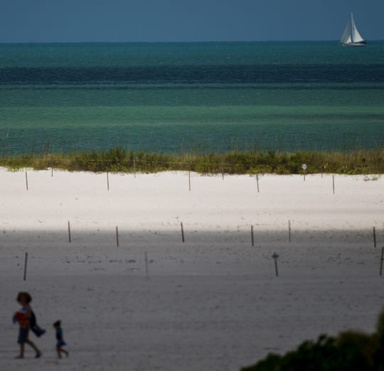 A partly cloudy day on April 30, 2019, throws shadows on the beach as a sailboat passes by on the Gulf of Mexico on the south end of Fort Myers Beach next to Big Carlos Pass.