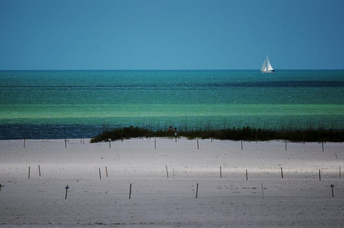 A partly cloudy day on Tuesday, April 30 throws shadows on the beach as a sailboat passes by on the Gulf of Mexico on the south end of Fort Myers Beach next to Big Carlos Pass.