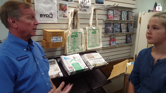 Ella Thiele talks with Richard Johnson in front of Bailey's reusable bags