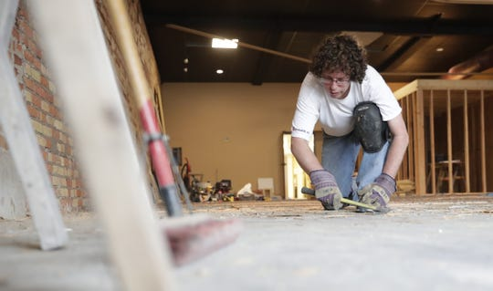 Eben Erhard, a friend of XO Fitness owners Karin and Ryan Jennings, helps with construction work at the gym's new location at 115 N. Wisconsin St. in De Pere.