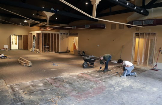 Ryan Jennings and Eben Erhard work on the floor of the  new location for XO Fitness, 115 N. Wisconsin St., in De Pere. Jennings and his wife, Karin, own the gym and already were preparing to move when a fire destroyed the building they had been operating out of.
