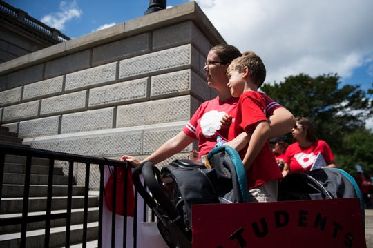 Erica McCall, of Greenville, S.C., looks up the stairs of the Capitol with her son, Jack, 5, as teachers rally in Columbia on Wednesday.