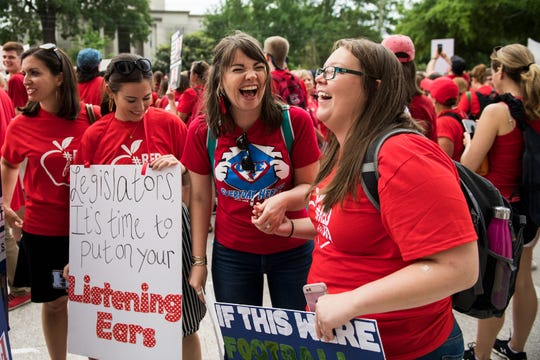 Lindsey Finley, first grade teacher at Duncan Chapel Elementary School, right, and fourth grade teacher Amanda Thomas of OP Earle Elementary School laugh during a teachers rally in Columbia Wednesday, May 1, 2019.