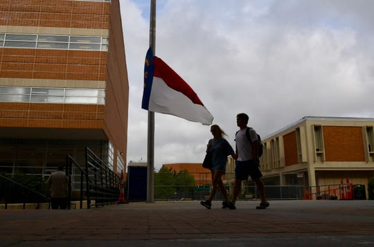 Students walk past a North Carolina flag that flies at half staff on Wednesday, May 1, 2019, on the campus of UNC Charlotte.