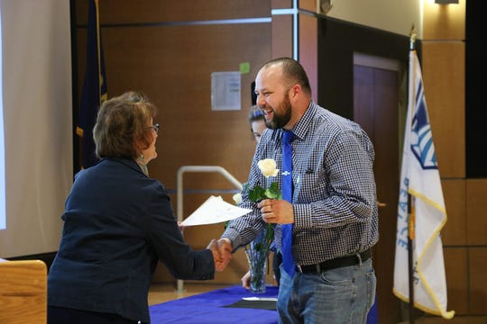 PTK inductee Christopher Disalvatore receives the Phi Theta Kappa award and rose from honorary PTK member, Dr. Susan Wolff, CEO/Dean at Great Falls College MSU.