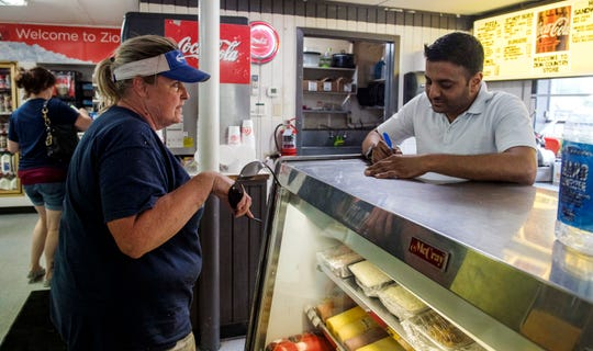Deepan Patel, general manager of the recently remodeled Zion Country Store, takes a customer's order at the deli counter on Wednesday, The Zion Country Store got new management on April 19. Patel said along with the new look, there is also larger sandwiches and more variety.