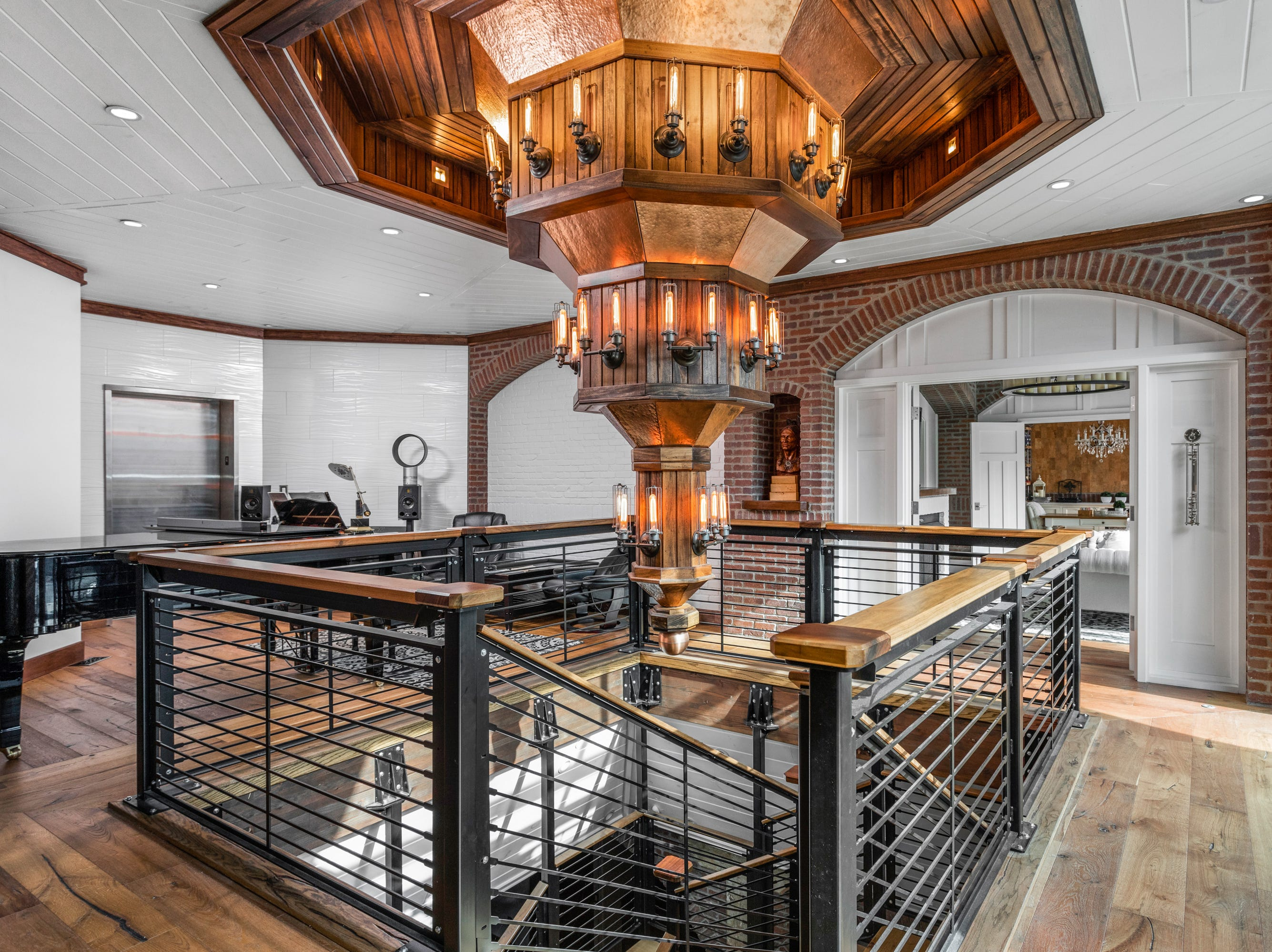 The current owner created this signature wood chandelier, visually anchored by the staircase.