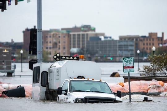 A City of Davenport vehicle gets submerged under water as flood waters from the Mississippi River covers streets, Tuesday, April 30, 2019, in downtown Davenport, Iowa.