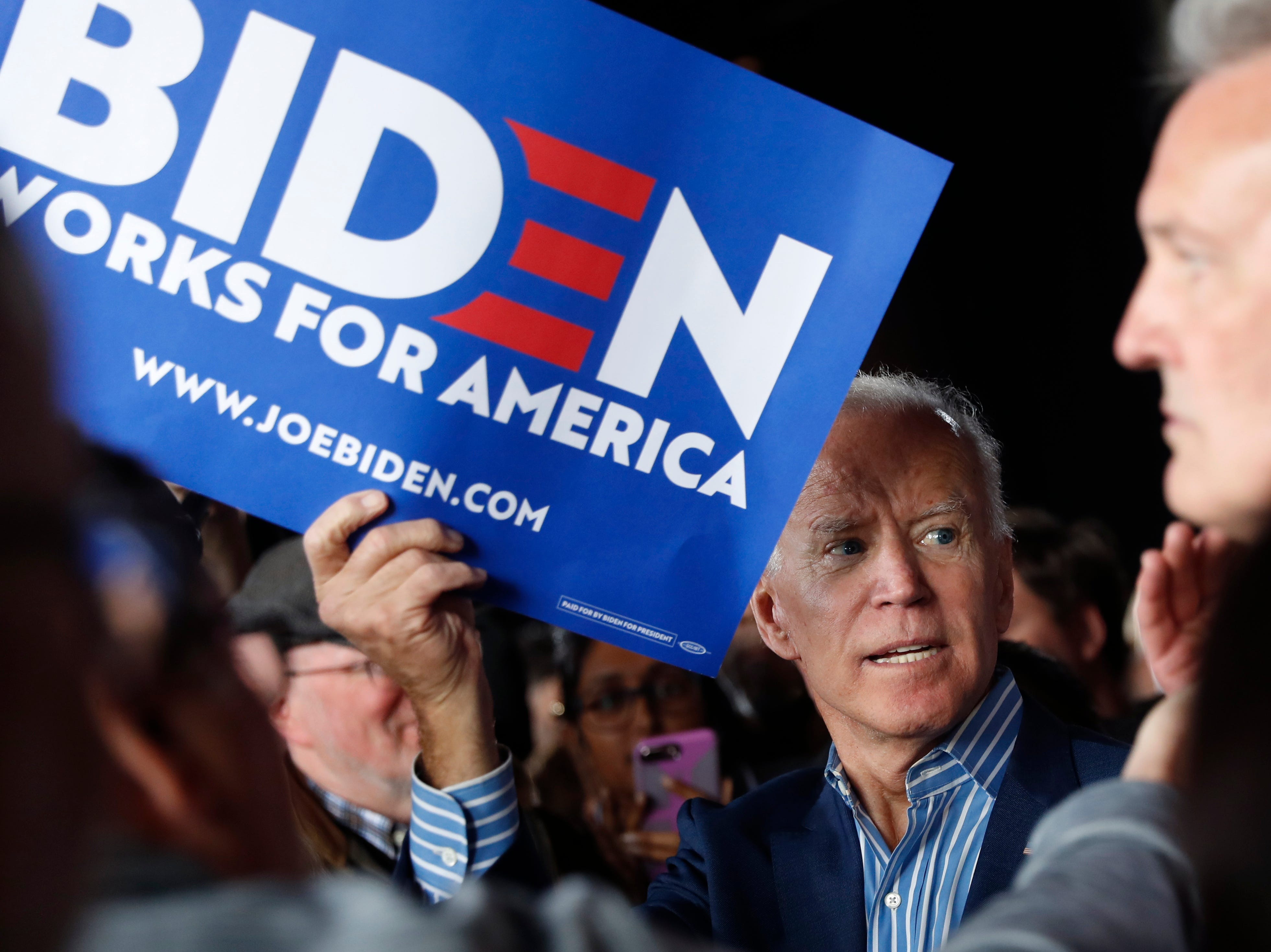 Former Vice President and Democratic presidential candidate Joe Biden holds a sign to be autographed during a rally, Wednesday, May 1, 2019, in Iowa City, Iowa.