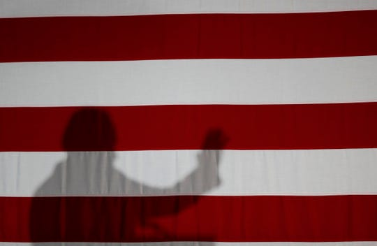Former Vice President and Democratic presidential candidate Joe Biden casts a shadow on a flag as he speaks during a rally, Wednesday, May 1, 2019, in Iowa City, Iowa.