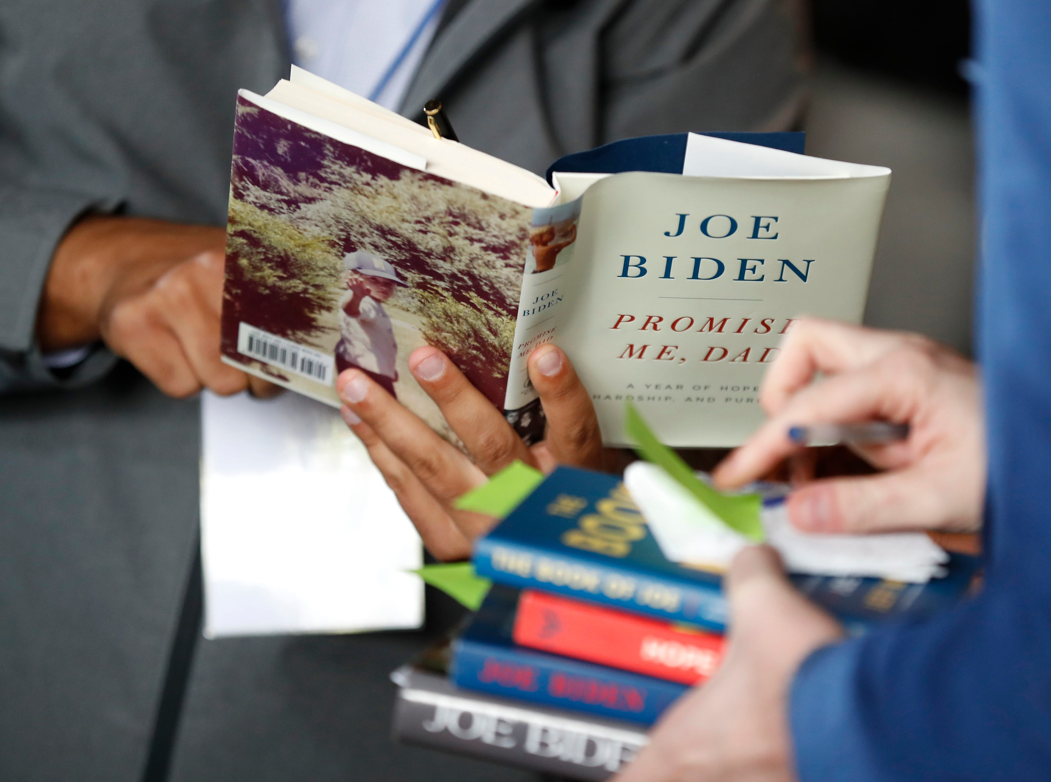 Campaign staffers hold books for former Vice President and Democratic presidential candidate Joe Biden to autograph during a rally, Wednesday, May 1, 2019, in Iowa City, Iowa.
