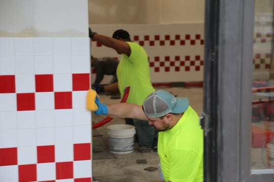 Workers were putting up new tile on Wednesday, May 1 at Five Guys Burgers & Fries in Ithaca.