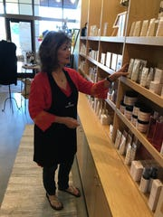 TerriWissel of Ridgeland, a makeup consultant, straightens skincare products at the Merle Norman studio in Madison.