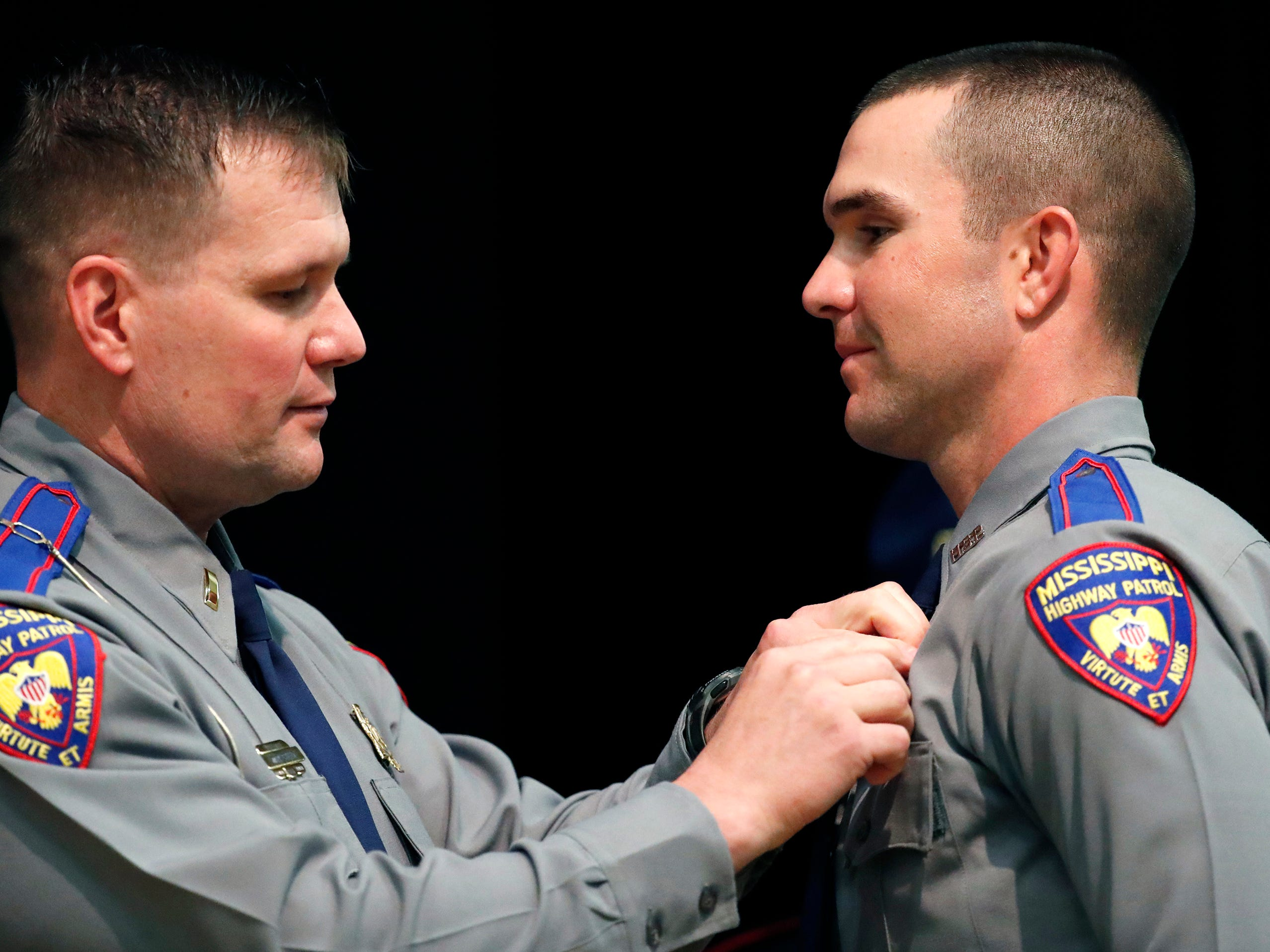 Cadet Jonathan Mark Steed, right, smiles as his father, Mississippi Bureau of Investigation Lt. Mark Steed, left, has difficulty in pinning the Mississippi Highway Patrol badge on him, Wednesday, May 1, 2019, during their graduation ceremony, in Pearl, Miss. The younger Steed was one of the 44 cadets sworn in as the newest Mississippi Highway Patrol troopers. The patrol's training lasts 22 weeks and involves classroom instruction, physical fitness, firearms and emergency operations training as well as a variety of police science courses.